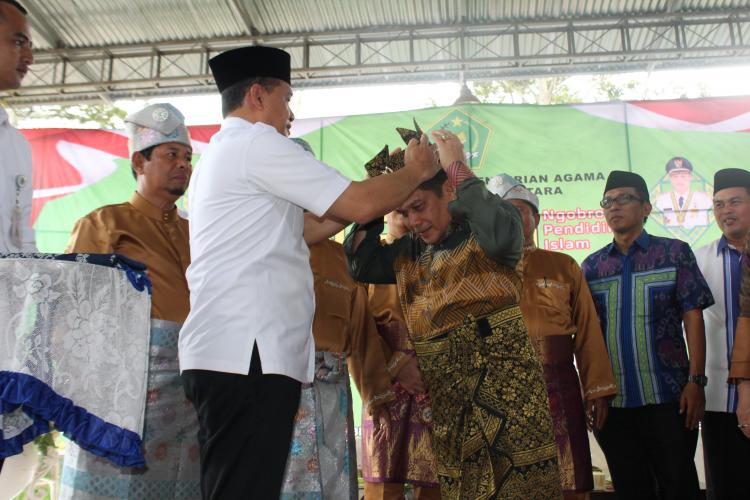 NGOPI, Bupati Batubara Pakaikan Songket Melayu Pada Kakanwil Kemenag Sumut