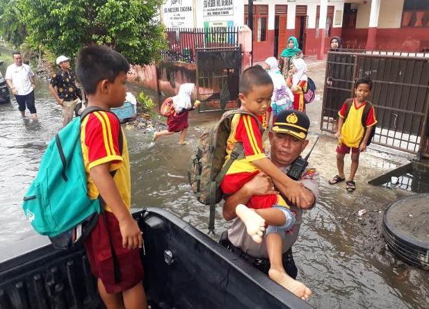 Terendam Banjir, Kapolsek Medan Timur Bantu Antar Siswa SD dengan Mobil Patroli