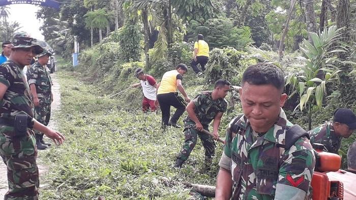 Jumat Bersih, Polsek Kutalimbaru dan Babinsa Bersihkan Jalan Raya Dusun V Sukarende