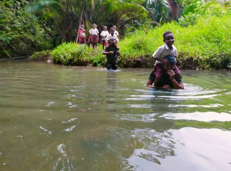 Minim Jembatan, Satgas Yonif  516/CY Rela Arungi Sungai Antar Anak-Anak ke Sekolah