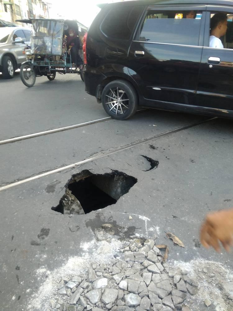Jalan Sutomo Samping Perlintasan Kereta Api Medan Amblas, Satu unit Mobil Terperosok ke Lobang Cukup Dalam